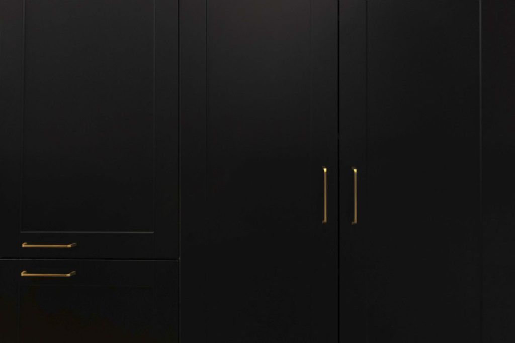 Fitted Kitchen in Marbella with black kitchen cabinets and golden handles.