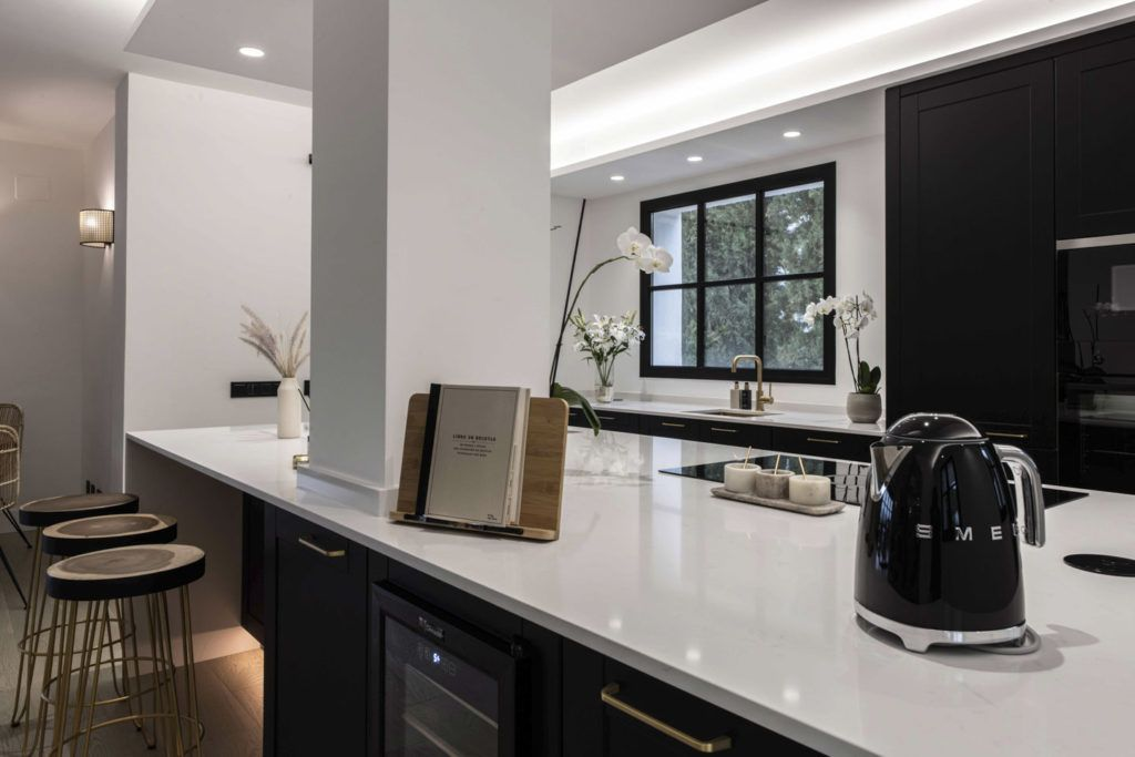 Fitted Kitchen in Marbella with black kitchen cabinets, white Silestone worktop and golden sink, tap and handles.
